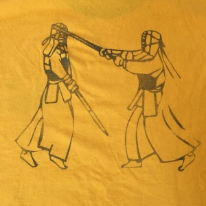 A drawing on the back of a shirt that shows two Kumdo competitors in armor fighting with bamboo swords.