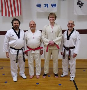 Four men in white taekwondo uniforms and belts. Two are wearing red belts and are standing between two black belt instructors.